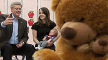 Conservative Leader Stephen Harper speaks to Lianne Hastman, holding her son Henry, during a roundtable in Beaumont, Alta. (Adrian Wyld/The Canadian Press)