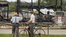 Men on bicycles stop to look at the remains of the main building at the St. Jacobs Farmers Market on Sept. 2, 2013, after an overnight fire destroyed the building. (GEOFF ROBINS/THE CANADIAN PRESS)