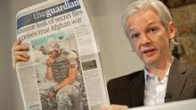 "Australian founder of whistleblowing website, 'WikiLeaks', Julian Assange, holds up a copy of today's Guardian newspaper during a press conference in London on July 26, 2010. The founder of a website which published tens of thousands of leaked military files about the war in Afghanistan said Monday they showed that the ""course of the war needs to change"". In all, some 92,000 documents dating back to 2004 were released by the whistleblowers' website Wikileaks to the New York Times, Britain's Guardian newspaper, and Germany's Der Spiegel news weekly. Assange also used a press conference in London to dismiss the White House's furious reaction to the disclosures. (Leon Neal/Leon Neal/AFP/Getty Images)"