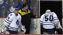 Toronto Maple Leafs goalies Jonas Gustavsson and James Reimer head to the dressing room following their loss to Vancouver Canucks in their NHL hockey game in Vancouv
