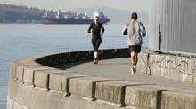 Joggers run along the Stanley Park sea wall during the Vancouver 2010 Winter Olympics, February 20, 2010. Vancouver is listed as one of the cities most at risk from rising sea levels because of climate change. (Greg Bos/REUTERS)