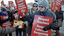 Retired teacher Graham Bonesteel , left, hands out timbits to striking elementary school teachers picketing in front of York Region District School Board offices in Aurora, December 13, 2012. (J.P. MOCZULSKI For The Globe and Mail)