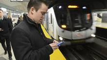 While waiting at the Bloor St subway station for the southbound Yonge St., Morgan Quinn is able to connect to the internet on Dec. 10, 2013, through the TTC's new WiFi spot. (Fred Lum/The Globe and Mail)