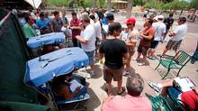 Buyer agents crowd around seated auctioneers at a foreclosure auction in front of the Maricopa County Courthouse in Phoenix, Ariz. (AARON J. LATHAM/AARON J. LATHAM/AP)