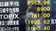 A businessman is reflected on a board showing prices on the Tokyo Stock Exchange. (-/AFP/Getty Images)