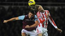 West Ham United's Andy Carroll (L) and Stoke City's Peter Crouch challenge for an aerial ball during their English Premier League soccer match at Upton Park in London November 19, 2012. (TOBY MELVILLE/REUTERS)