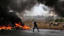 A Palestinian protester throws stones during clashes with Israeli security forces at the northern entrance of the West Bank town Al-Bireh, on the northern outskirts of Ramallah on October 26, 2015. (ABBAS MOMANI/AFP/Getty Images)