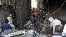 In this photo released by the Syrian official news agency SANA, Syrian citizens gather at an alley destroyed by two cars bombs, in the Jaramana neighbourhood, suburb of Damascus, Nov. 28, 2012. (SANA/AP)