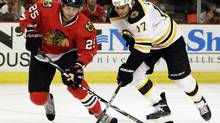 Boston Bruins' Milan Lucic (17) and Chicago Blackhawks' Viktor Stalberg (25) compete for the puck during the first period of an NHL hockey game in Chicago, Saturday, Oct. 15, 2011. The Stanley Cup final opens Wednesday in Chicago as the Blackhawks host the Boston Bruins. (Nam Y. Huh/AP)