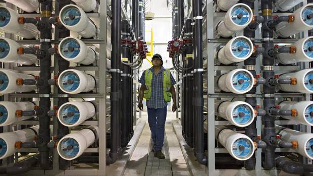 Water treatment operator Carl Shirt walks through the reverse osmosis units at the water treatment plant in Saddle Lake Alberta, July 21, 2016. Saddle Lake reserve gets its water from the lake, which is classified as surface water and INAC considers this a risky water source.