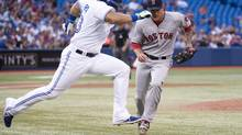 The Blue Jays' Melky Cabrera, left, runs past Red Sox starting pitcher Jake Peavy, right, beating a wild throw at first base but was tagged out at second in a rundown during the third inning of their game in Toronto on Tuesday. (Nathan Denette/THE CANADIAN PRESS)