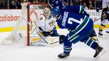 Nashville Predators goalie Carter Hutton, left, stops a shot by Vancouver Canucks' Dan Hamhuis during first period NHL hockey action in Vancouver, B.C., on Thursday January 23, 2014 (The Canadian Press)