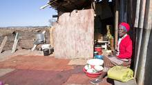 Mantsie Malatsi washes dishes outside her shack in Chiawelo, an area of Soweto, South Africa, where the movie District 9 was filmed. (Erin Conway-Smith/Erin Conway-Smith)