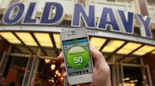 A reporter demonstrates a shopping app in front of an Old Navy store in San Francisco. Smartphones can scan bar codes and offer real-time discounts but most Canadians won't bother using apps while shopping this holiday season, a new survey suggests. (Jeff Chiu/AP)