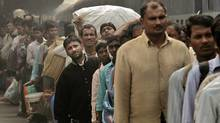 Indian passengers wait for a train at a startion in New Delhi on Oct. 31. A study by Allianz shows that only 12 per cent of Indians contribute to a pension. (Manish Swarup/Manish Swarup/Associated Press)