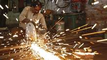 An employee works inside a metal workshop in Kolkata, India, Jan. 3, 2011 (RUPAK DE CHOWDHURI)