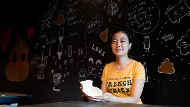 Lien Nguyen, owner of Poop Caf, holds a toilet shaped bowl imported from Vietnam.