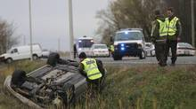 Authorities investigate an overturned vehicle in Saint-Jean-sur-Richelieu, Que., on Oct. 20, 2014. Two Canadian soldiers were injured in a hit-and-run.