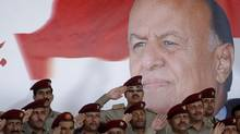 Military officers salute in front of poster of Yemen's President Abd-Rabbu Mansour Hadi during a military parade celebrating the 50th anniversary of North Yemen's revolution in Sanaa September 26, 2012. (Khaled Abdullah/REUTERS)