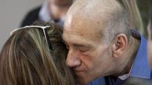 Former Israeli prime minister Ehud Olmert kisses his former bureau chief Shukla Zaken after hearing the verdict in his trial at Jerusalem's District Court on Tuesday. (Ariel Schalit/Associated Press)