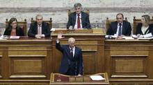 Greek Prime Minister George Papandreou acknowledges applauding members of his party parliamentarians after addressing lawmakers in the parliament prior to a confidence vote in Athens Nov. 4, 2011. (YIORGOS KARAHALIS/YIORGOS KARAHALIS/REUTERS)