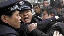 Police officers break up a protest in front of the Peace Cinema in Shanghai on Feb. 20, 2011. Protesters gathered in central Beijing and Shanghai on Sunday after calls spread online across China urging pro-democracy gatherings inspired by protest rallies across the Middle East. (CARLOS BARRIA/Carlos Barria/Reuters)