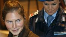 Defendant Amanda Knox, a 22-year-old American accused of killing her housemate, is accompanied by a penitentiary officer prior to a hearing at the court in Perugia, Italy. (LUCA BRUNO)