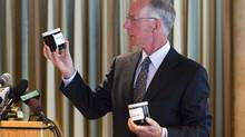Newspaper publisher David Black displays jars of oil in Vancouver on Aug. 17 while unveiling a plan to build a B.C. refinery. (BEN NELMS/REUTERS)