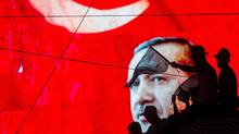 People wave Turkish flags in front of an electronic billboard displaying the face of President Recep Tayyip Erdogan at a rally on the streets of Kizilay Square in reaction to the failed military coup on July 17, 2016 in Ankara, Turkey. Clean up operations are continuing in the aftermath of Friday's failed military coup attempt which claimed the lives of more than 250 people. In raids across Turkey 6,000 people have been arrested in relation to the failed coup including high-ranking soldiers and judges, Turkey's Justice Minister Bekir Bozdag has said. (Chris McGrath/Getty Images)