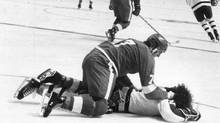 Dan Maloney of the Detroit Red Wings tries to pick a fight with an unconscious Brian Glennie of the Toronto Maple Leafs. Glennie was hospitalized with a concussion. Maloney was charged with assault causing bodily harm for which he was acquitted on June 30, 1976. (John Maiola For The Globe and Mail)