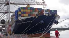 A dock worker walks near a container ship at the Port of Southampton, U.K., in this file photo. (Jason Alden/Bloomberg)