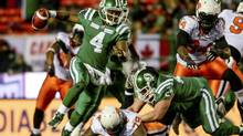 Saskatchewan Roughriders quarterback Darian Durant (4) runs the ball past BC Lions defensive tackle Eric Taylor (79) during the second half of their west semi-final CFL football game in Regina, Saskatchewan November 10, 2013. (STRINGER/CANADA/Reuters)
