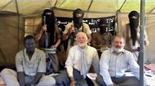This exclusive photo, never published before, is taken from a video made by the al-Qaeda terrorists who kept Robert Fowler and Louis Guay in captivity for 130 days. The video, obtained by Mali-based journalist Serge Daniel, was made on Feb. 3, 2009 in a tent in the Sahara desert in northern Mali. Mr. Fowler is sitting in the middle of the front row, with Mr. Guay on the right. On the left is their UN driver from Niger, who was released earlier than the Canadians. Behind them are four members of al-Qaeda carrying machine guns. The kidnapper right behind Mr. Fowler is carrying a sword.