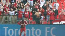 Toronto FC's Jonathan Osorio, who scored the goal that tied the game, clutches a TFC scarf thrown on the field after the team won 2-1 over Columbus Crew in the pouring rain at the Trillium Cup match MLS action in Toronto on Saturday, July 27, 2013. (Michelle Siu/THE CANADIAN PRESS)