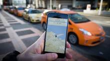 The Uber app is displayed on an iPhone as taxi drivers wait for passengers in downtown Vancouver. (DARRYL DYCK for The Globe and Mail)