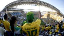 In this photograph taken with a fisheye lens, a Brazil supporter reacts as Brazil players are announced before the World Cup opening match between Brazil and Croatia at Itaquerao Stadium in Sao Paulo, Brazil, Thursday, June 12, 2014. (Julio Cortez/AP)