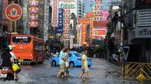 Residents walk in floodwaters along a street in the Chinatown section of Bangkok on Oct. 28, 2011. (Tang Chhin Sothy/AFP/Getty Images)