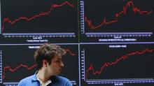 A man walks in front of an index board at the reception hall of the Athens Stock exchange May 28, 2012. (JOHN KOLESIDIS/REUTERS)