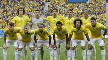 The Brazilian team pose for a group photo prior to the group A World Cup soccer match between Cameroon and Brazil at the Estadio Nacional in Brasilia, Brazil, Monday, June 23, 2014. (Andre Penner/AP)