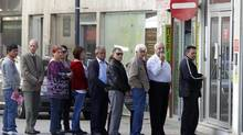 Depositors wait for the opening of a branch of Laiki Bank in Nicosia on March 29, 2013. (BOGDAN CRISTEL/REUTERS)