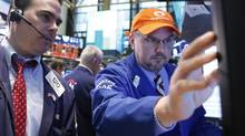 Trader Michael Iozzi and specialist trader John Urbanowicz (R) at the New York Stock Exchange Wednesday. (BRENDAN MCDERMID/REUTERS)