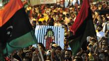 People wave flags of the Kingdom of Libya and hold a cartoon illustration of Libya's leader Moammar Gadhafi as they gather near the courthouse in Benghazi August 22, 2011 to celebrate the entry of rebel fighters into Tripoli. (ESAM OMRAN AL-FETORI/REUTERS/ESAM OMRAN AL-FETORI/REUTERS)