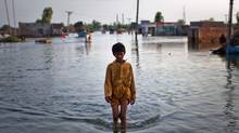 A boy sloshes through the floodwaters in a village outside Punjab, Pakistan, on Aug. 21. (Daniel Berehulak/Getty Images)