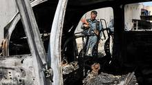 An Afghan policeman stands guard near the charred remains of a vehicle at UN headquarters in Mazar-e-Sharif after protesters attacked the compound on April 2, 2011. (Shah Marai/AFP/Getty Images)