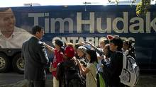 "Students point at Ontario Conservative leader Tim Hudak's picture on his campaign bus as Hudak makes a stop on his campaign bus at Queen""s Park in Toronto on Sept. 15, 2011. (Nathan Denette/Nathan Denette/The Canadian Press)"