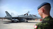 A Canadian soldier looks at a CF-18 as it sits loaded for flight at Camp Fortin on the Trapani-Birgi Air Force Base in Trapani, Italy, on Thursday, September 1, 2011. (Sean Kilpatrick/The Canadian Press/Sean Kilpatrick/The Canadian Press)