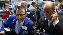 Barclay's specialist trader Michael Pistillo gives a opening price to traders on the floor of the New York Stock Exchange, July 10, 2012. (BRENDAN MCDERMID/REUTERS)