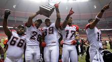 Calgary Stampeders, from left, Stanley Bryant, Brandon Smith, Charleston Hughes, Maurice Price and Marquay McDaniel celebrate with the trophy after defeating the B.C. Lions in the CFL Western Final football game in Vancouver, B.C., on Sunday November 18, 2012. (The Canadian Press)