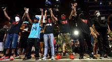 Protesters raise their arms during a march in Charlotte, N.C. on Thursday, Sept. 22, 2016. The curfew has ended for Friday in Charlotte following a night of mostly peaceful protests of the shooting of Keith Lamont Scott by an officer. Charlotte Mayor Jennifer Roberts issued the curfew order Thursday night, to be in effect from midnight until 6 a.m. each day that the state of emergency continues. (Jeff Siner/AP)