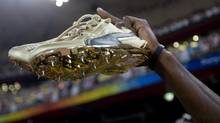 Jamaica's Usain Bolt holds up his gold running shoes after he and his team won the 4x100 meter relay race at the Beijing Olympics in Beijing, China Friday Aug. 22, 2008. (Jonathan Hayward/The Canadian Press)